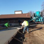 Sidewalk cement being poured in front of new construction area